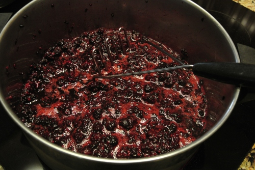 The mashed of dewberries coming up to a boil.
