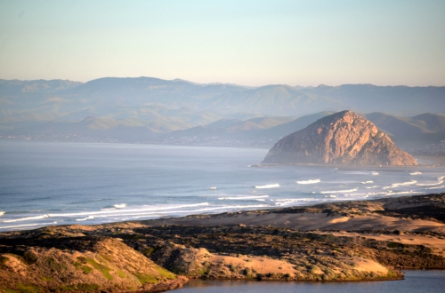 Morro Rock and the surfline beyond the dunes.