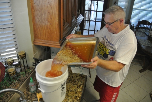 Pouring off  the honey and wax bits into the pail. There is a fine sieve screen that sits on the top of the pail to catch the small stuff.